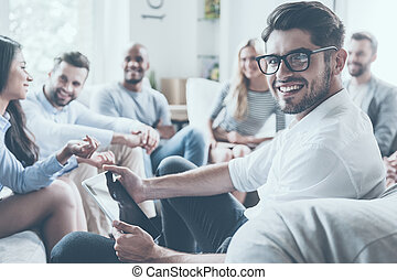 Confident psychologist. Group of young cheerful people sitting in circle and discussing something while young man holding digital tablet and looking over shoulder with smile