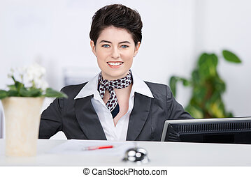 Confident Receptionist Smiling At Counter