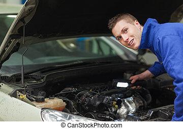 Confident repairman examining car engine