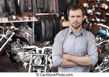 Confident sales executive. Confident young men standing in front of the motorcycles and holding his arms crossed