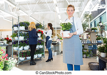 Confident Salesgirl Holding Flower Pot In Florist Shop