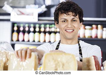 Confident Salesman Arranging Cheese In Shop