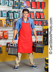 Confident Salesman Holding Toolboxes In Store