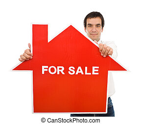 Confident salesman with house for sale sign