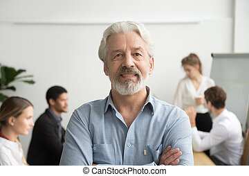 Confident senior businessman leader looking at camera, team at b