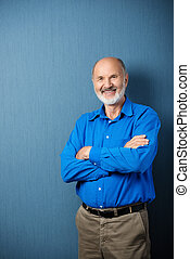 Confident senior male teacher standing with folded arms in...