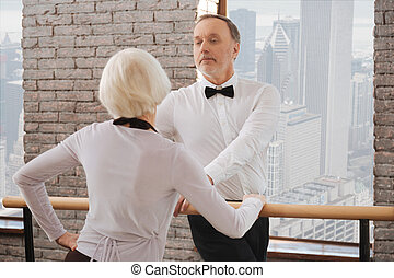Confident senior man dancing with aging woman in the ballroom