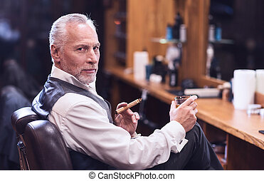 Confident senior man smoking a cigar
