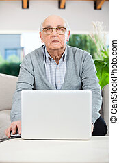 Confident Senior Man Using Laptop At Nursing Home Porch