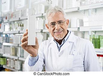 Confident Senior Pharmacist Holding Medicine Box In Pharmacy