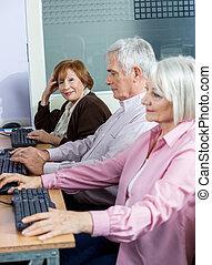 Confident Senior Woman Sitting With Classmates At Computer Desk