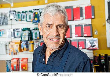 Confident Senior Worker Smiling In Hardware Shop