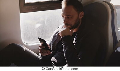 Confident serious Caucasian businessman texting on smartphone mobile office app sitting on modern train window seat.