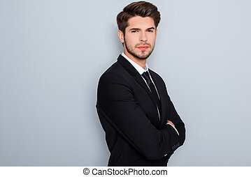 Confident serious successful businessman in suit with crossed hands