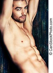 confident - Sexual muscular nude man posing over dark...