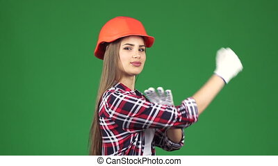 Confident sexy female constructionist showing her biceps we can do it gesture