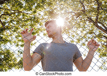 Confident shirtless sportsman in shorts standing outdoors