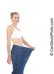 Confident smiling blonde wearing too big trousers