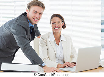 Confident smiling business couple with laptop