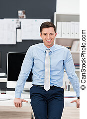Confident smiling businessman in his office