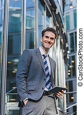 businessman stands in front of an office building with a tablet