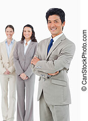 Confident smiling businessman with his employees behind him...