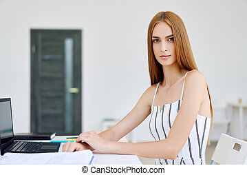 Confident smiling businesswoman posing in a modern office