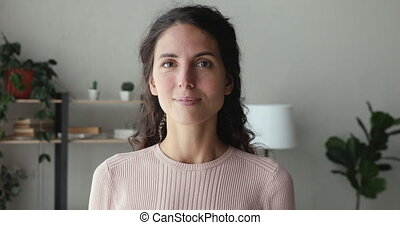 Confident smiling woman looking at camera standing at home office