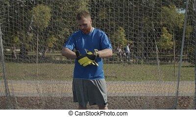 Confident soccer goalkeeper adjusting gloves