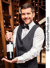 Confident sommelier. - Confident male sommelier holding wine...