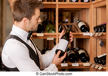 Confident sommelier. Thoughtful young sommelier holding a wine bottle and examining it