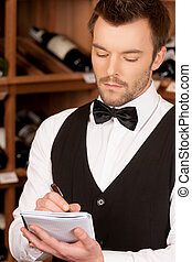 Confident sommelier. Thoughtful young sommelier writing...