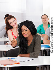 Confident Student Gesturing Thumbs Up In Classroom