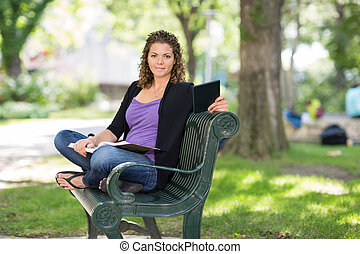 Confident Student Sitting On Bench At Campus