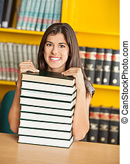 Confident Student Sitting With Stacked Books In Library
