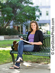 Confident Student Studying On Bench At Campus