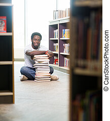 Confident Student With Stacked Books Sitting In Library