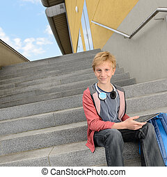 Confident student with tablet sitting on steps