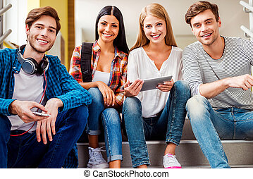 Confident students. Low angle view of four happy young people looking at camera and smiling while sitting on the stairs