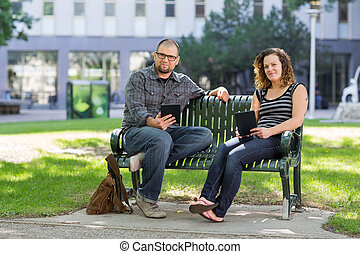 Confident Students Sitting On Bench At University Campus