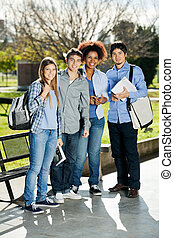 Confident Students Standing In Campus
