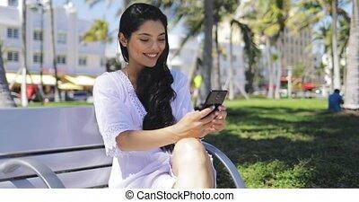 Confident stylish girl using phone in park - Pretty stylish...