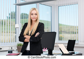 Confident successful young female business executive standing with folded arms in a modern office surrounded by windows