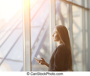 successful business woman with a smartphone, standing in front of a window in a modern office.