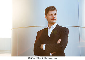 Confident successful young businessman standing with arms crossed