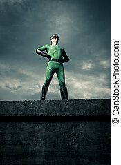 Green confident superhero standing against a cloudy sky with arms akimbo.