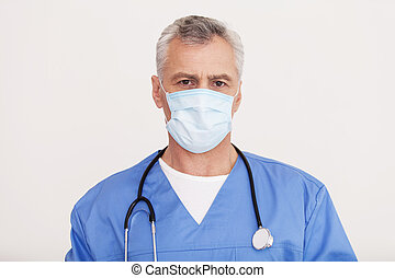 Confident surgeon. Portrait of senior grey hair doctor in surgical mask looking at camera while standing isolated on white