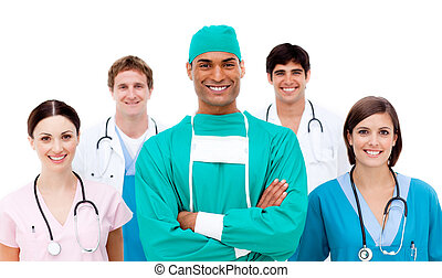 Confident surgeon with his team in the background smiling at...