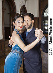Confident Tango Dancers Performing In Restaurant