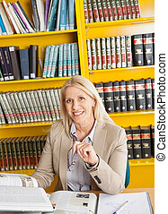 Confident Teacher With Books Sitting At Table In Library